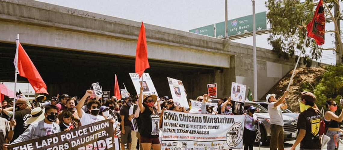 [ID: Centro CSO members march by a highway and hold signs and red flags]