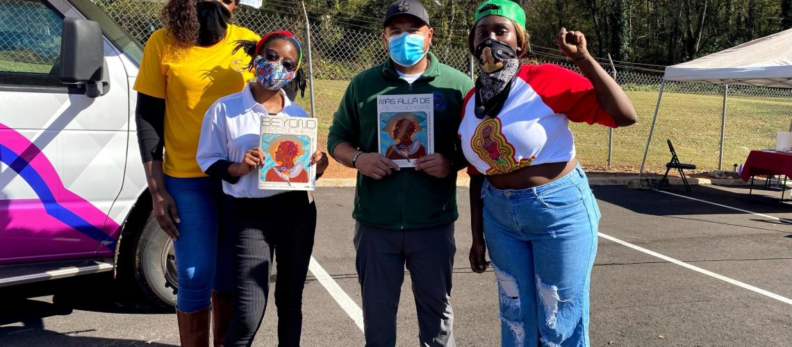 [ID: Black Inmate Commissary Fund members wear masks and hold up posters]
