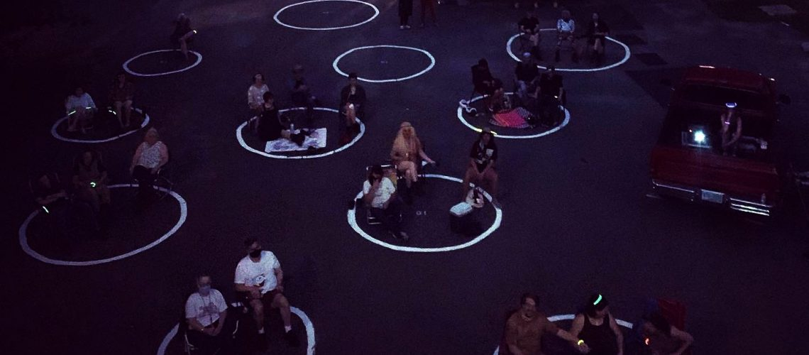 [ID: Dark image of a Backlot Cinema, people sitting in circles socially distanced]