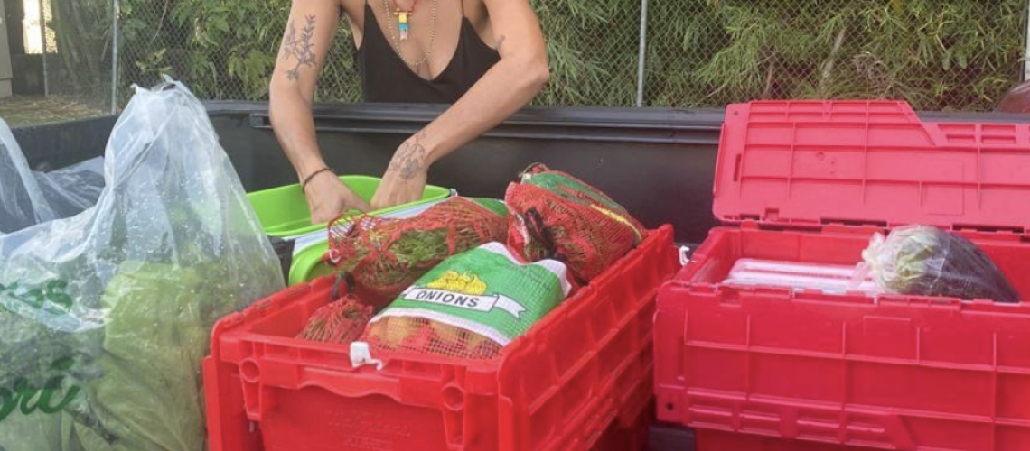 [Image description: Volunteer prepares food on the back of a pick-up truck as part of their Food Security program in collaboration with the group Espicynipples.]