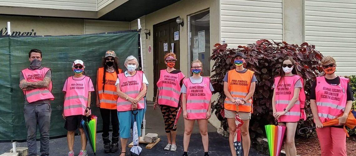 [Image description: Nine TBAF volunteers wear masks and pink and orange vests that either read: