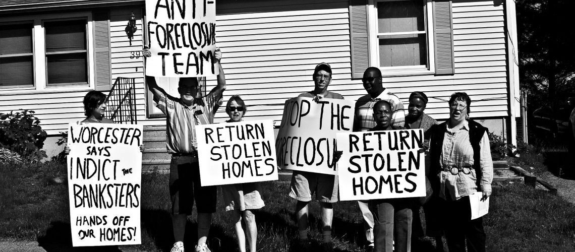 [ID: Black and white photograph of members holding signs in front of a home. Some signs read: