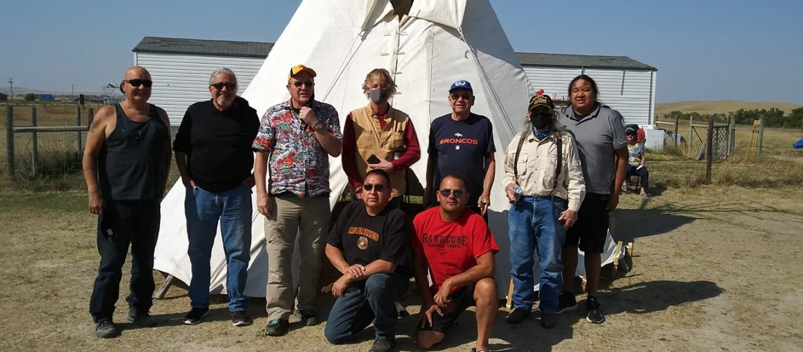 [ID: Members of All Relations United pose in front of a white teepee]