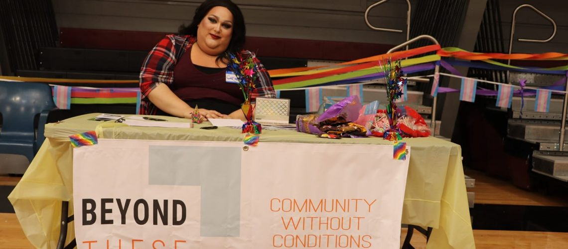 [Image description: A picture of Beyond These Walls' Programs Manager Carlee tabling at Maclaren Youth Correctional Facility's 5th annual Pride Celebration.]