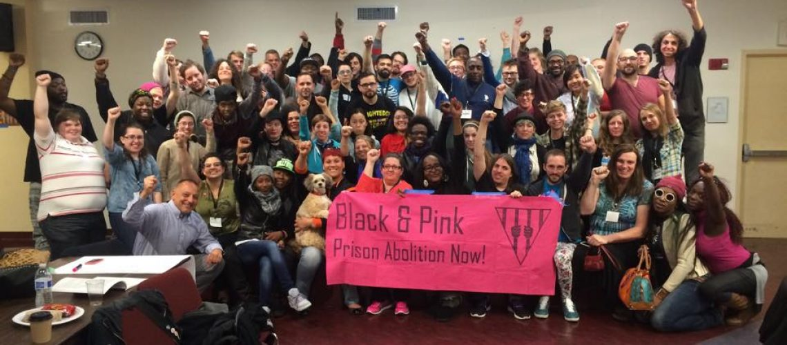 [Image description: Members of Black and Pink Massachusetts pose with fists in air and hold a pink banner that reads: