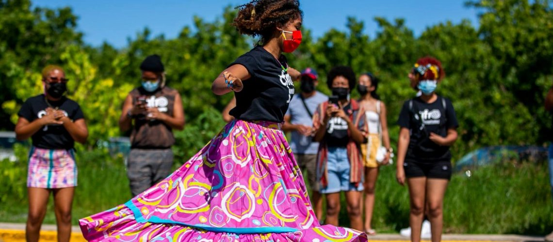 [Image description: Youth dances in a colorful pink skirt, a black shirt, and a red mask, as an audience of people look on. The event AfroJuventudes is the closure of a 9-month political antiracist school where 51 students from all over Puerto Rico meet virtually every Saturday to develop a healthy racial identity that strengthens and affirms their self-worth/image; as well as to understand racism, and its relationship to sexism and other forms of oppression.]