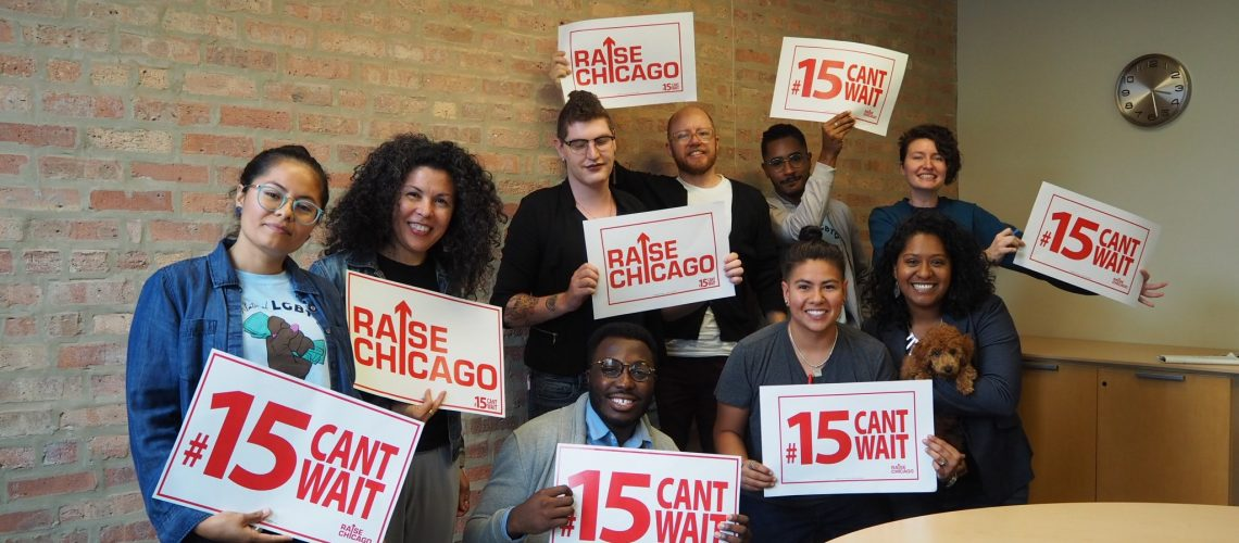 [ID: Nine members of the National LGBTQ Workers Center hold up white signs with red text that read: