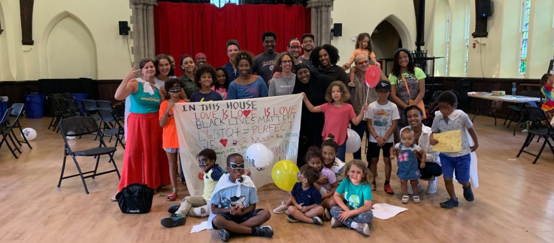 [ID: Intergenerational group of people hold up a sign that reads: