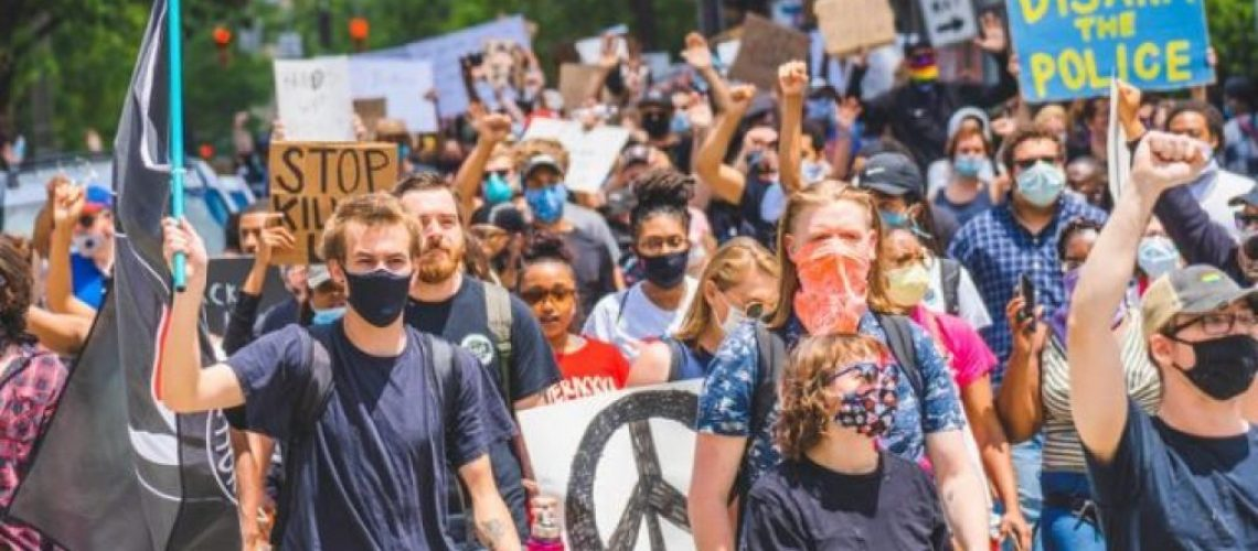 Protestors wearing masks with signs that read: