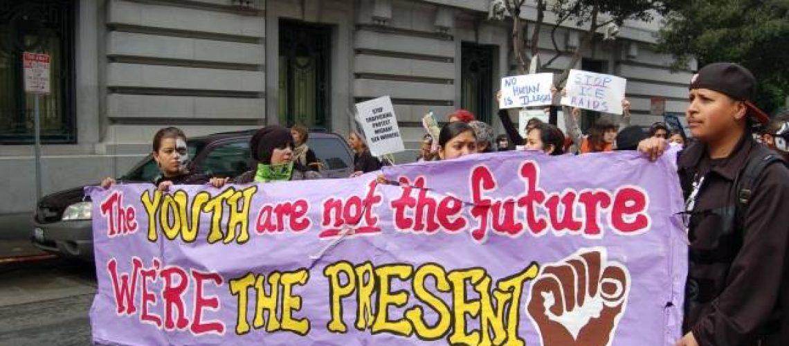 [Image description: Protestors hold large purple banner that reads: