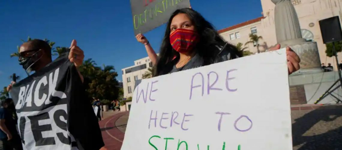 [ID: Person wearing a red mask holds a sign that reads: