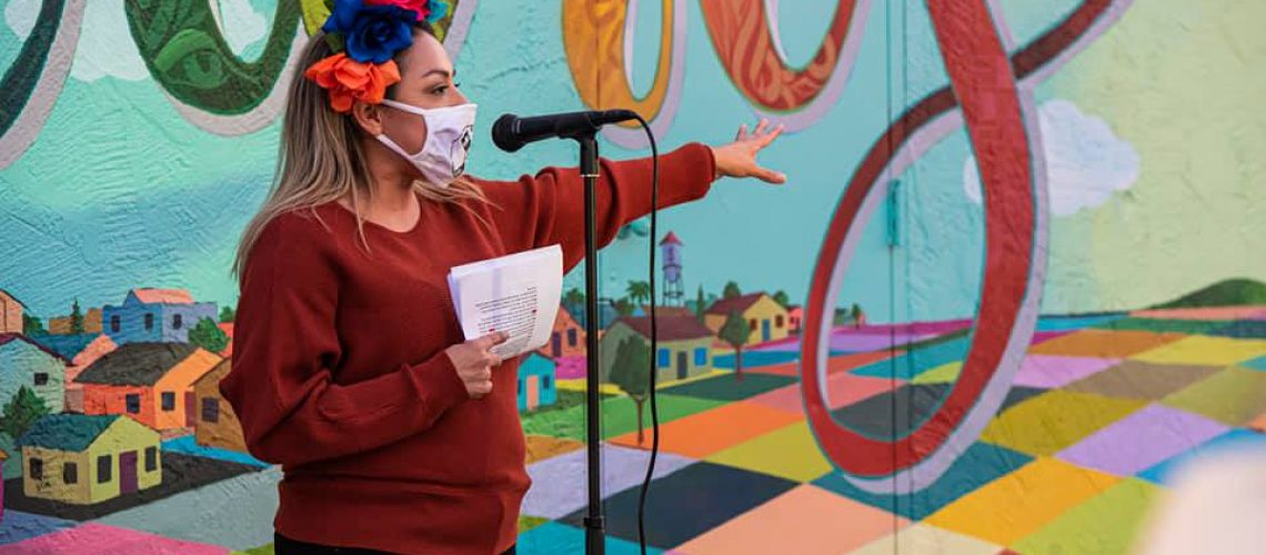 [ID: Person wearing a flower headdress, a mask and red sweater stands in front of a colorful mural speaking into a mic]