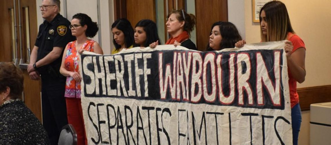[Image description: United Fort Worth members stage a protest and hold up a sign that reads